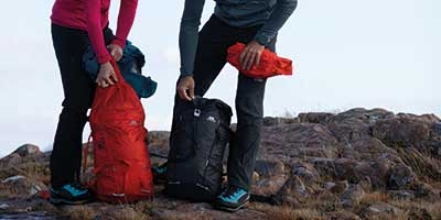 male and female mountaineers with their backpacks at their feet
