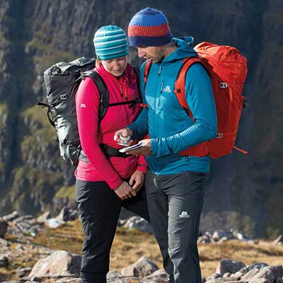man and woman looking at map wearing mountaineering backpacks