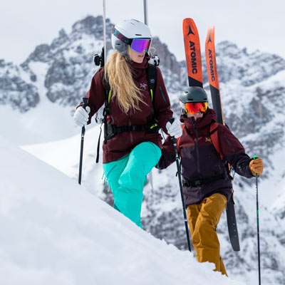 A woman and man carrying skis
