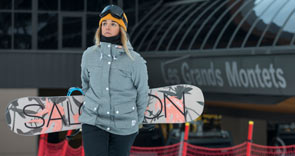 A woman carrying a snowboard