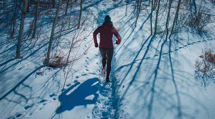 a runner trail running through wintry forest