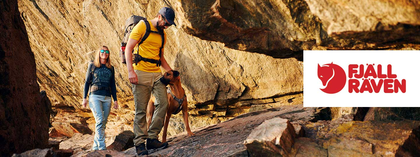 couple walking dog across rocky terrain in sunlight