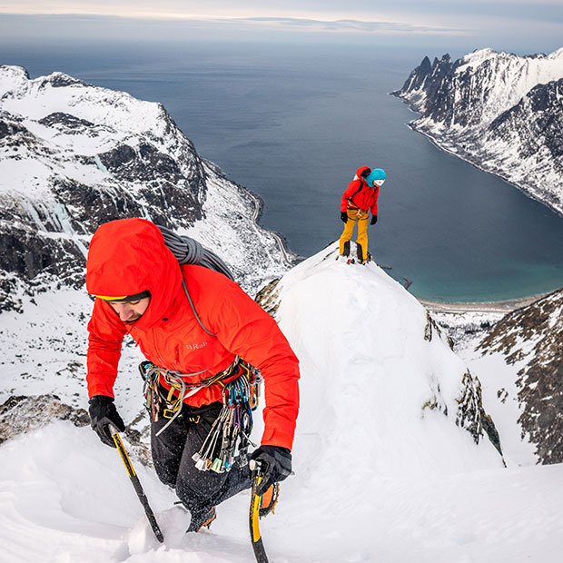 Two mountaineers wearing Rab kit ascending mountain with sea in background