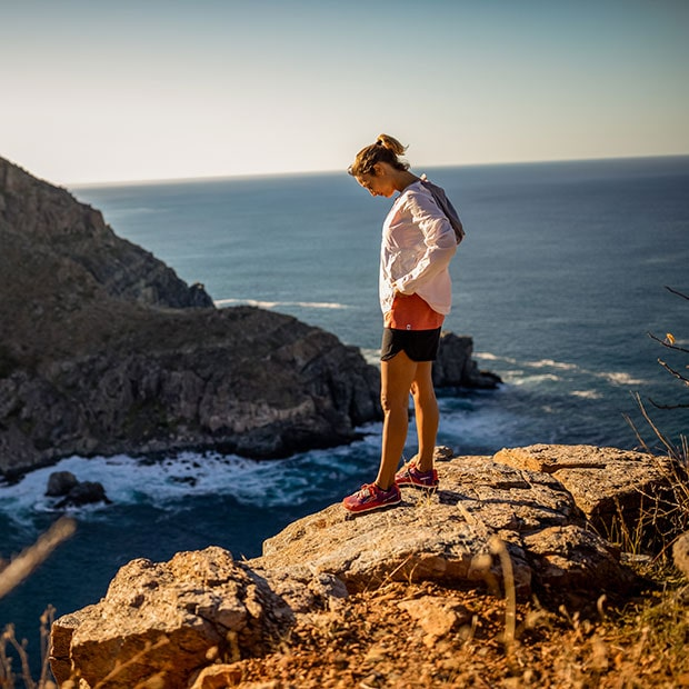 woman standing on cliff edge with sea in background