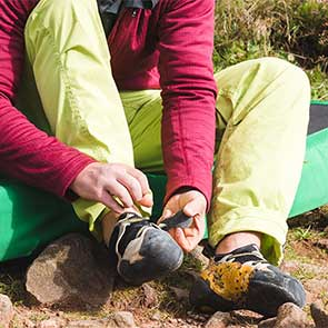 climber putting on climbing shoes