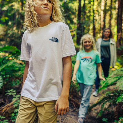 a boy and girl walking through woods