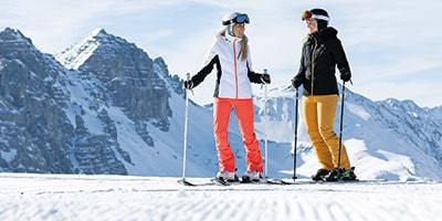 two women standing on piste ready to ski down