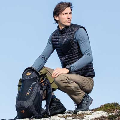 A man kneeling by rucksack