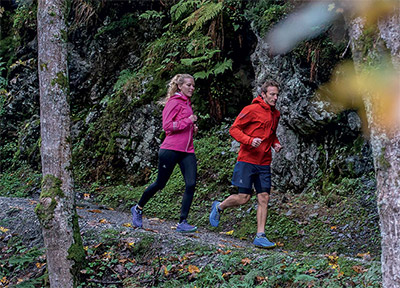 A man and woman trail running