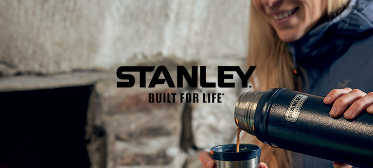 Stanley logo with woman pouring hot tea from a stanley flask in background
