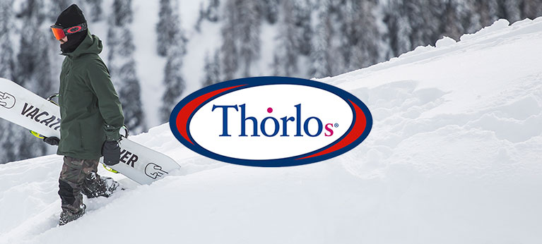 Thorlos logo with snowboarder walking with board in background