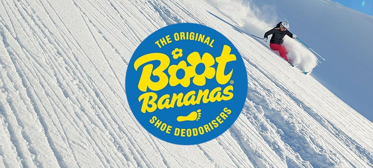 Boot Bananas logo with skier heading down powder slope in background