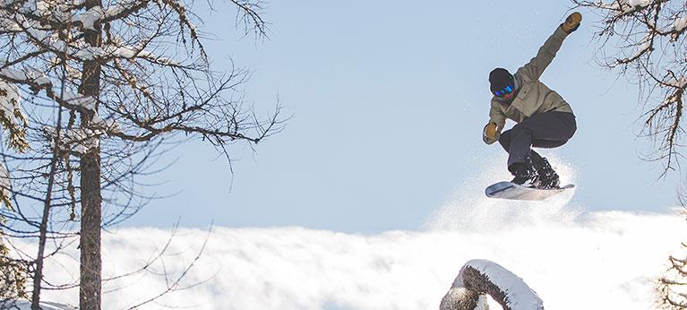 A snowboard jumping off a log