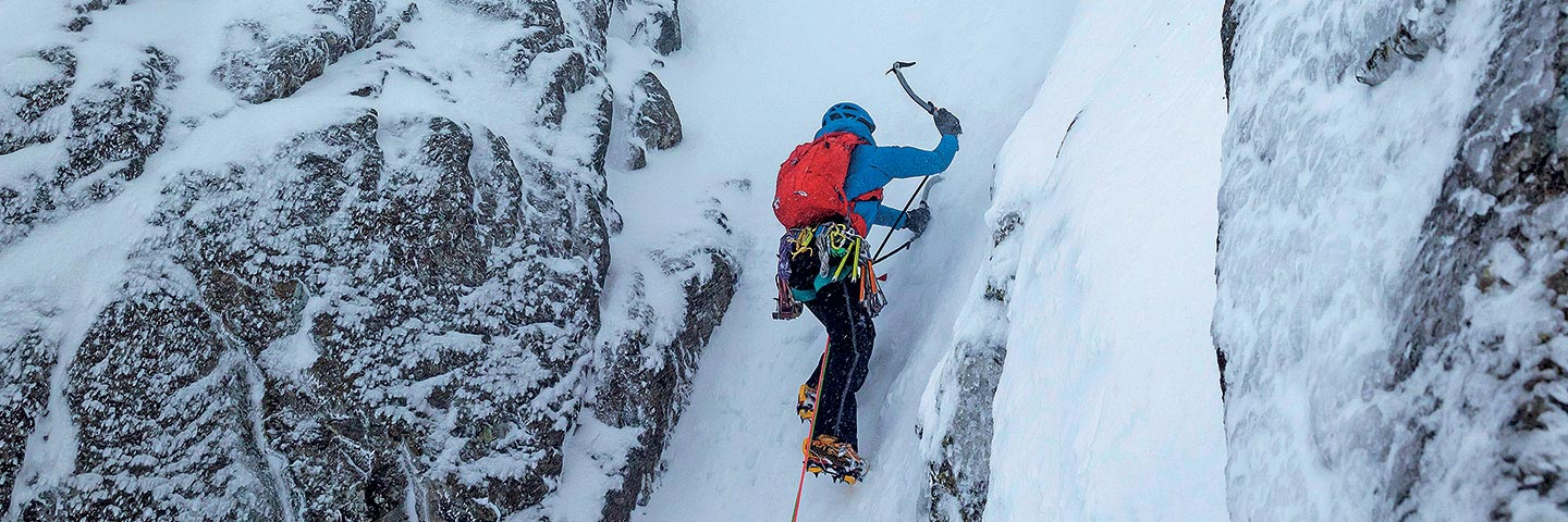 person using ice axe and crampons to climb icy gully