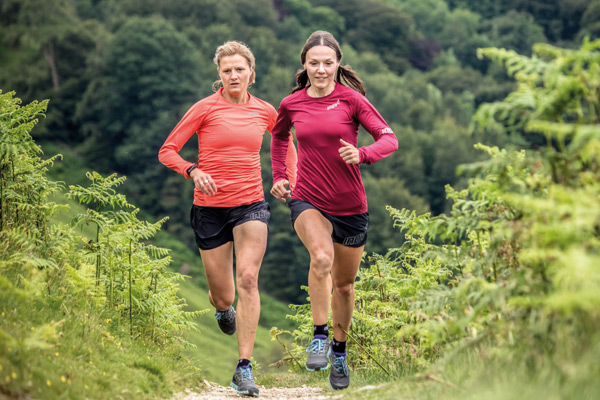 two women running on trail