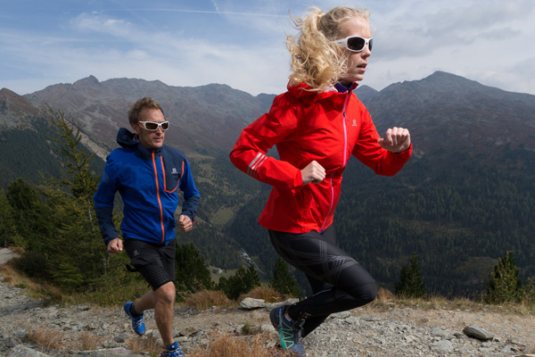 man and woman running over mountainous terrain