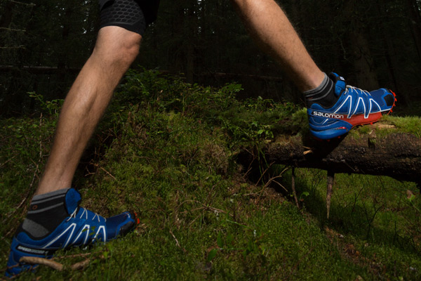 two feet with salomon running trainers running over fallen tree branch