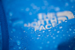 blue fabric with water droplets and the north face logo