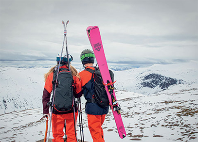 A man and woman backcountry skiing