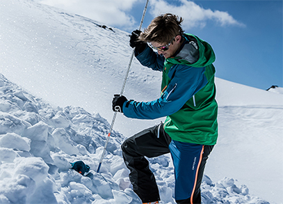 A man using an avalanche probe