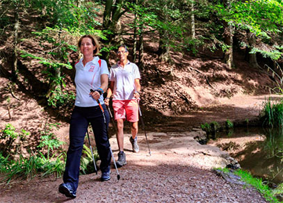 A man and woman nordic walking along a path