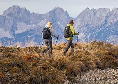 A man and woman hiking with walking poles