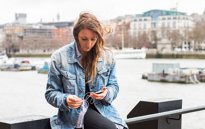 laura kennington sitting on a waterside railing looking at her phone