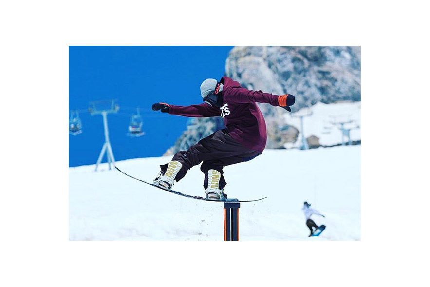 snowboarder riding down a rail