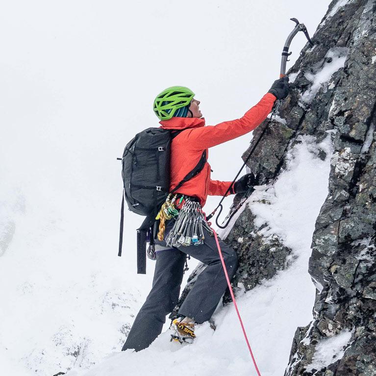 woman scrambling up rocky hillside